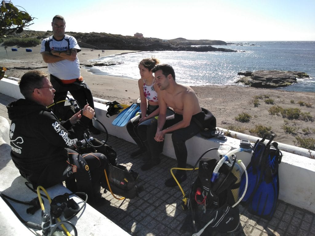Fábio and Carla going through diving theory on the beach